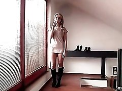 Beauty in short dress and boots smokes
