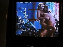 Bo Derek topless lying in bed with a guy as he kisses her,